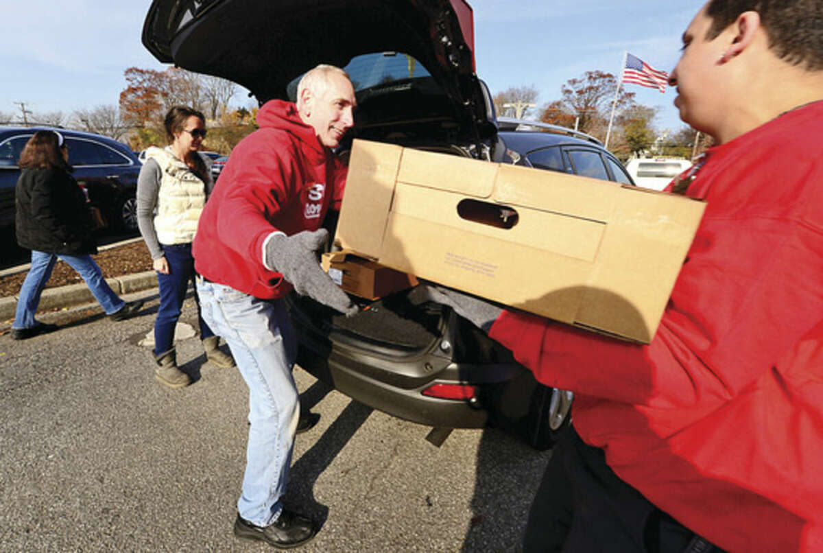 Hour photo / Erik Trautmann Employees Ken Bloch and Lynden Lund load up frozen turkeys for Christine Brown of Roton Middle School during Stew Leonard's 35th Annual Turkey Brigade Thursday. Stew Leonard's stores gave out more than 1,900 turkeys to more than 100 churches, civic groups, elderly housing and senior nutrition programs, and schools the Norwalk, Newington and Danbury, Connecticut and Yonkers, New York communities to help provide Thanksgiving day meals for families in need.