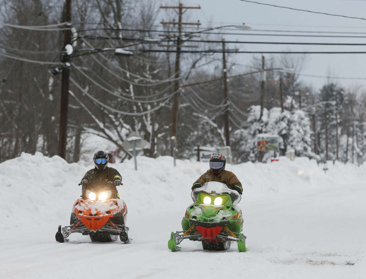 Volunteer firefighters ride snowmobiles alone Clinton Street on Thursday, Nov. 20, 2014, in West Seneca, N.Y. A new blast of lake-effect snow pounded Buffalo for a third day piling more misery on a city already buried by an epic, deadly snowfall that could leave some areas with nearly 8 feet of snow on the ground when it's all done. (AP Photo/Mike Groll)