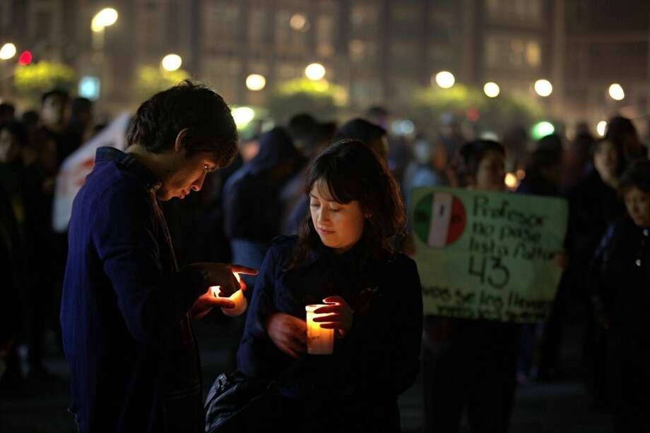 "A couple hold candles during a massive protest in Mexico City's main sqaure ""El Zocalo,"" during a march in the capital city to demand authorities find 43 missing college students, in Mexico City, Thursday Nov. 20, 2014. Mexico officially lists more than 22 thousand people as having gone missing since the start of the country's drug war in 2006, and the search for the missing students has turned up other, unrelated mass graves. in Mexico City, Thursday, November 20, 2014. (AP Photo/Eduardo Verdugo)"