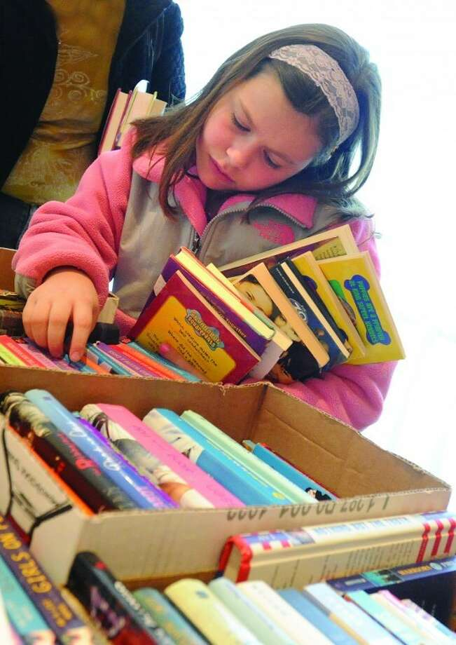 9-year-old Rachel Iannazzo stacks up on books Sunday at the Wilton Library book sale. hour photo/Matthew Vinci