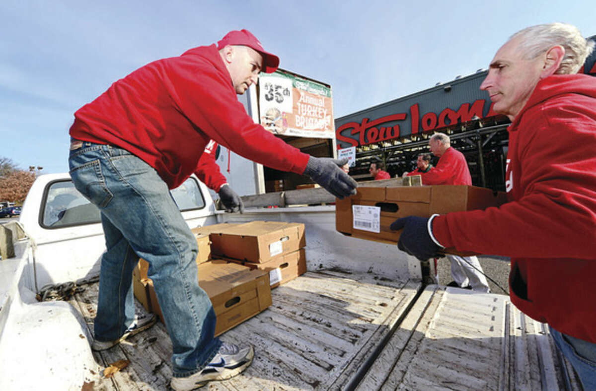Hour photo / Erik Trautmann Employees Peter Tournas and Ken Bloch load up frozen turkeys during Stew Leonard's 35th Annual Turkey Brigade Thursday. Stew Leonard's stores gave out more than 1,900 turkeys to more than 100 churches, civic groups, elderly housing and senior nutrition programs, and schools the Norwalk, Newington and Danbury, Connecticut and Yonkers, New York communities to help provide Thanksgiving day meals for families in need.