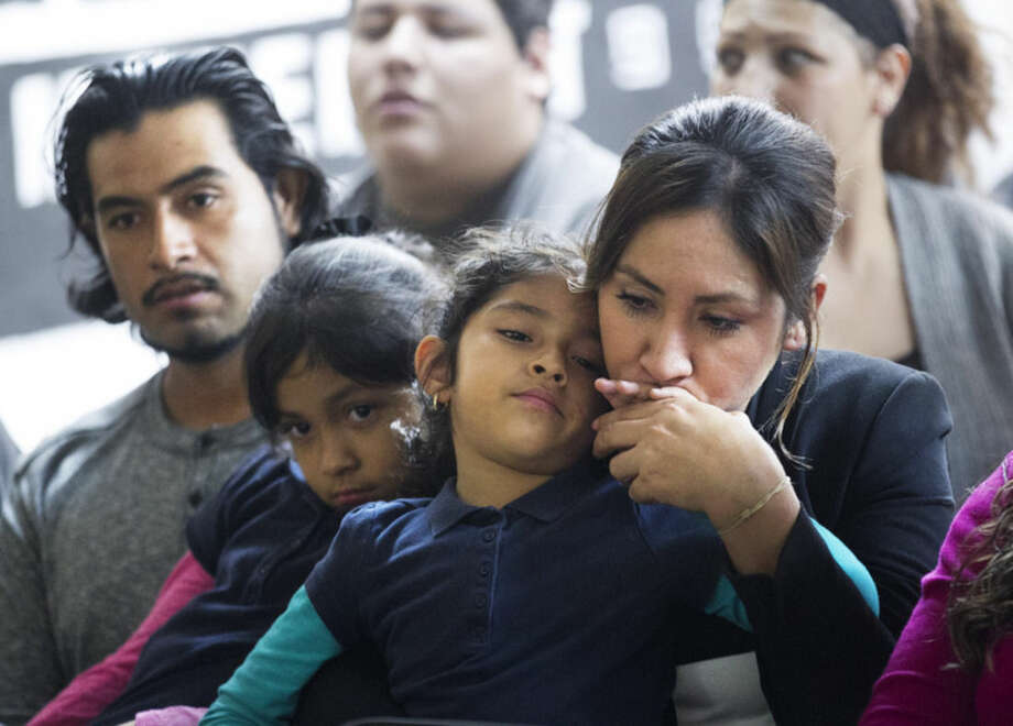 Ana Patino, right, of Phoenix, kisses the hand of her daughter, Natalie Cruz, 5, as Ana's husband and the girl's father, Rafael Cruz, left, sits with Camila Cruz, during a watch party for President Obama's speech on immigration at the Puente offices in Phoenix on Thursday, Nov. 20, 2014. (AP Photo/The Republic, David Wallace)