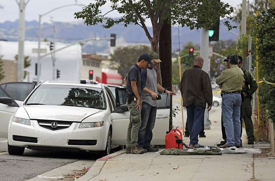 Investigators examine items removed from the car of a heavily armed man who was arrested in Santa Monica early Sunday. Photo: Reed Saxon, Associated Press