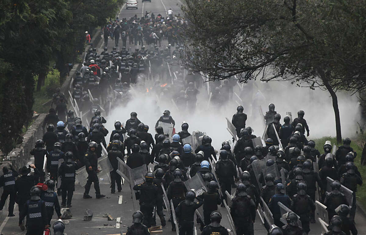 Scores of riot police march to confront protesters near the airport in Mexico City,Thursday, Nov. 20, 2014. Protesters, some with their faces covered in masks or bandannas, scuffled with police as they tried to block a main expressway to the Mexico City international airport. Protesters hurled rocks and fireworks at the police, at least one of whom was hit by the projectiles. Protesters marched in Mexico City to demand authorities find 43 missing students Thursday, a day traditionally reserved for the celebration of the country's 1910-1917 Revolution. (AP Photo/Marco Ugarte)