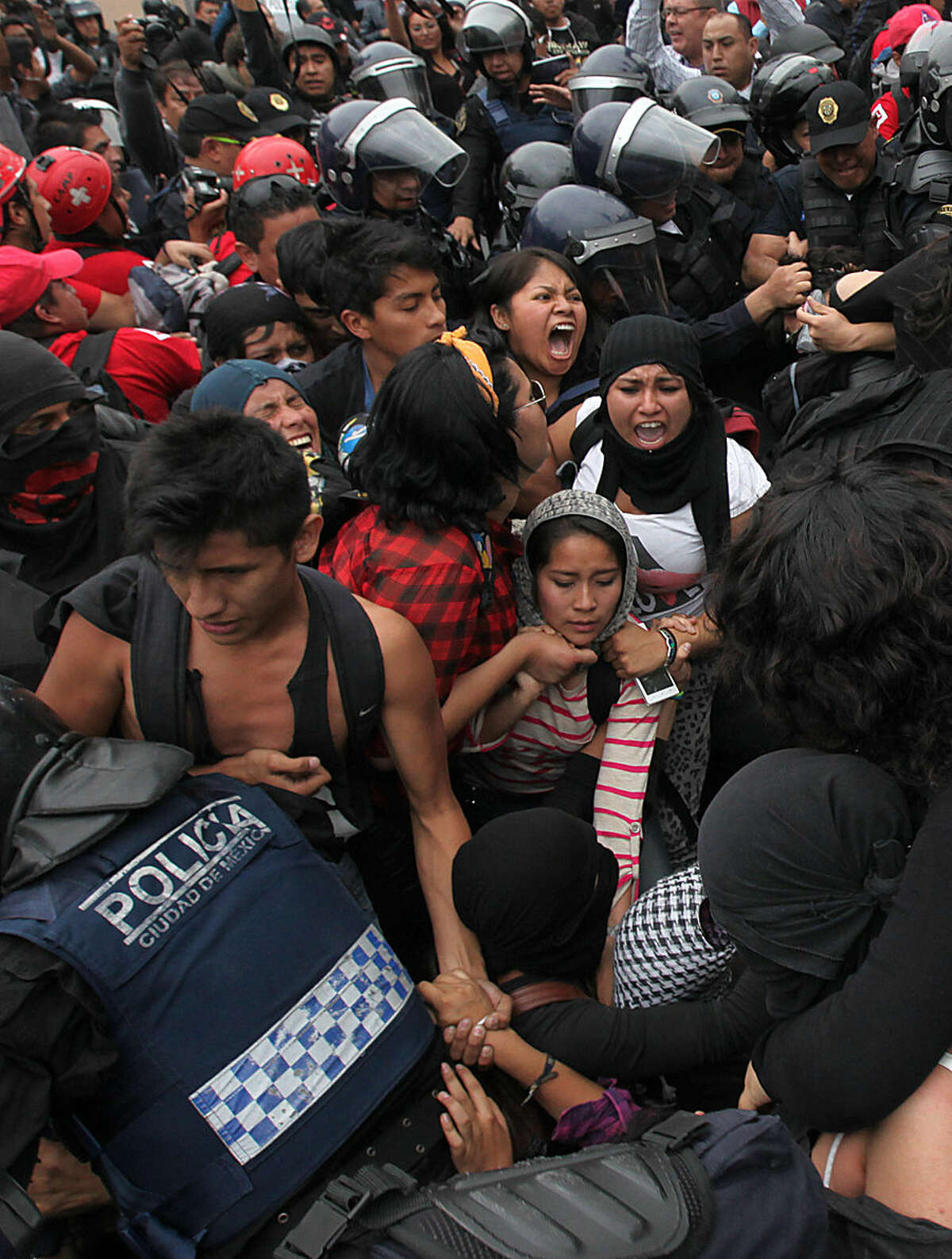 Riot police surround protesters who had clashed with police during a march near the airport in Mexico City, Thursday, Nov. 20, 2014. Protesters marched to demand authorities find 43 missing college students, trying to step up pressure on the government on a day traditionally reserved for the celebration of the 1910-17 Revolution. (AP Photo/Marco Ugarte)