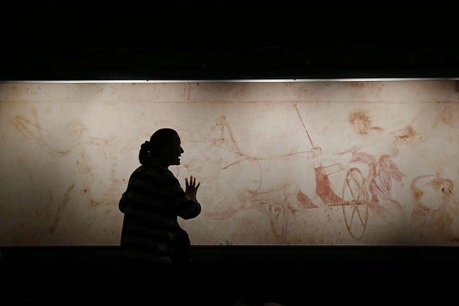 A schoolteacher explains the myth of Persephone in front of a replica of a mid-4th century B.C. wall painting of Hades abducting Persephone, whose original was found in a looted royal tomb, at the Vergina museum in northern Greece, Oct. 7, 2014. A similar scene has been discovered on a mosaic floor in a newly-excavated Macedonian tomb in Amphipolis, which has revived interest in ancient Greece's Macedonian dynasties. (AP Photo/Petros Giannakouris)