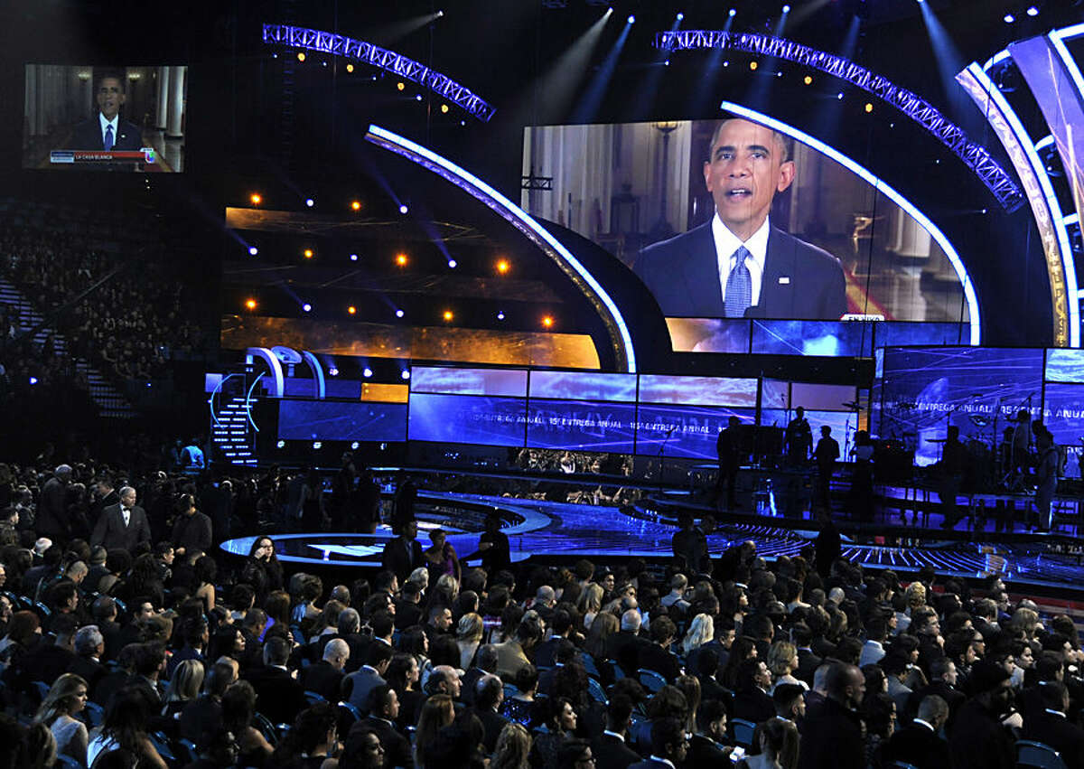 President Barack Obama appears on screen at the 15th annual Latin Grammy Awards at the MGM Grand Garden Arena on Thursday, Nov. 20, 2014, in Las Vegas. Obama unveiled his expansive executive actions on immigration Thursday night to spare nearly 5 million people in the U.S. illegally from deportation. (Photo by Chris Pizzello/Invision/AP)