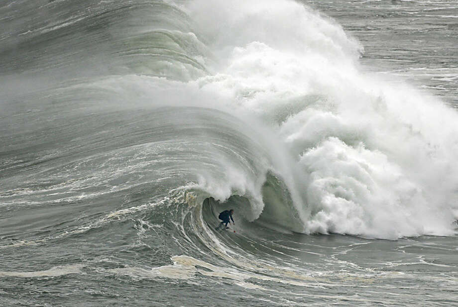 A surfer rides a wave during a tow-in surfing session at the Praia do Norte or North beach, in Nazare, Portugal, Thursday, Nov. 20, 2014. A tow-in is a surf technique in which the athlete is towed into a large wave by a partner driving a jet-ski or other watercraft with an attached tow-line. (AP Photo/Francisco Seco)