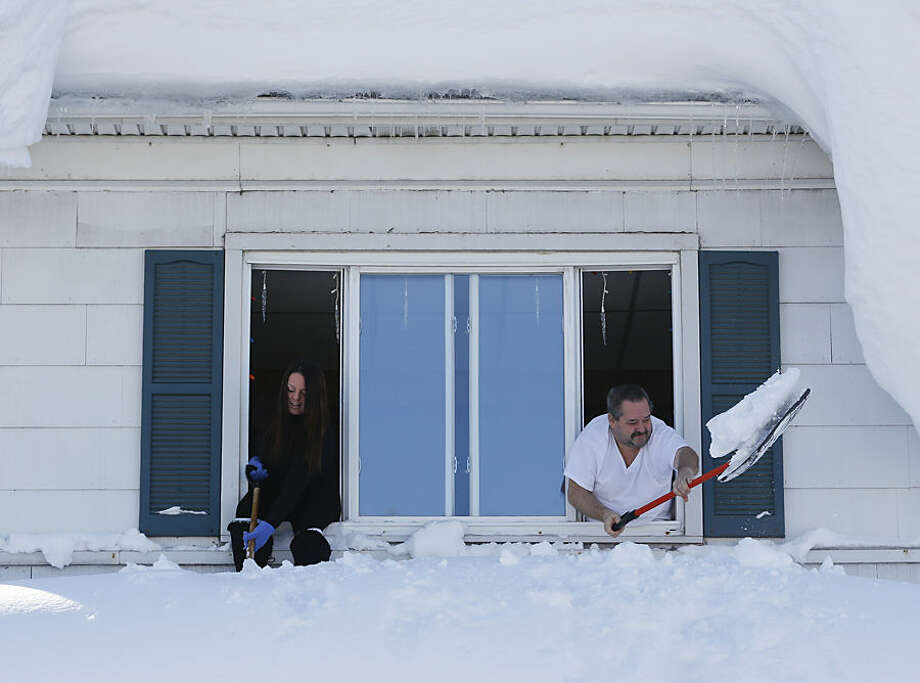 Residents clear snow from a porch roof while leaning from a second-story window in the south Buffalo area on Friday, Nov. 21, 2014, in Buffalo, N.Y. A snowfall that brought huge drifts and closed roads in the Buffalo area finally ended Friday, yet residents still couldn't breathe easy, as the looming threat of rain and higher temperatures through the weekend and beyond raised the possibility of floods and more roofs collapsing under the heavy loads. (AP Photo/Mike Groll)