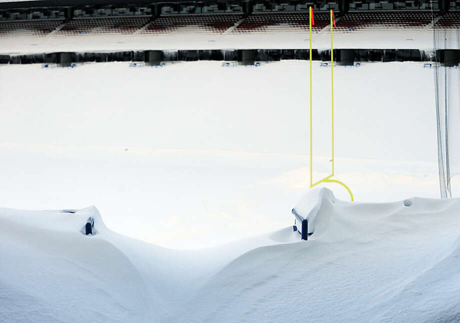 "An aisle is drifted over and seats are filled with snow at Ralph Wilson Stadium in Orchard Park, N.Y. Friday, Nov. 21, 2014. Snowed out in Buffalo, the Bills are heading to Detroit to play their ""home"" NFL football game against the New York Jets on Monday night, Nov. 24, 2014. (AP Photo/Gary Wiepert)"