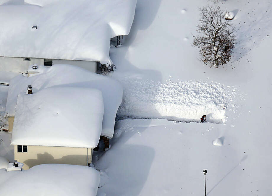 FILE - A man digs out his driveway in Depew, N.Y.,Wednesday, Nov. 19, 2014. The Buffalo area found itself buried under as much as 5½ feet of snow Wednesday, with another lake-effect storm expected to bring 2 to 3 more feet by late Thursday. (AP Photo/The Buffalo News, Derek Gee) MANDATORY CREDIT; TV OUT; MAGS OUT; MANDATORY CREDIT; BATAVIA DAILY NEWS OUT; DUNKIRK OBSERVER OUT; JAMESTOWN POST-JOURNAL OUT; LOCKPORT UNION-SUN JOURNAL OUT; NIAGARA GAZETTE OUT; OLEAN TIMES-HERALD OUT; SALAMANCA PRESS OUT; TONAWANDA NEWS OUT