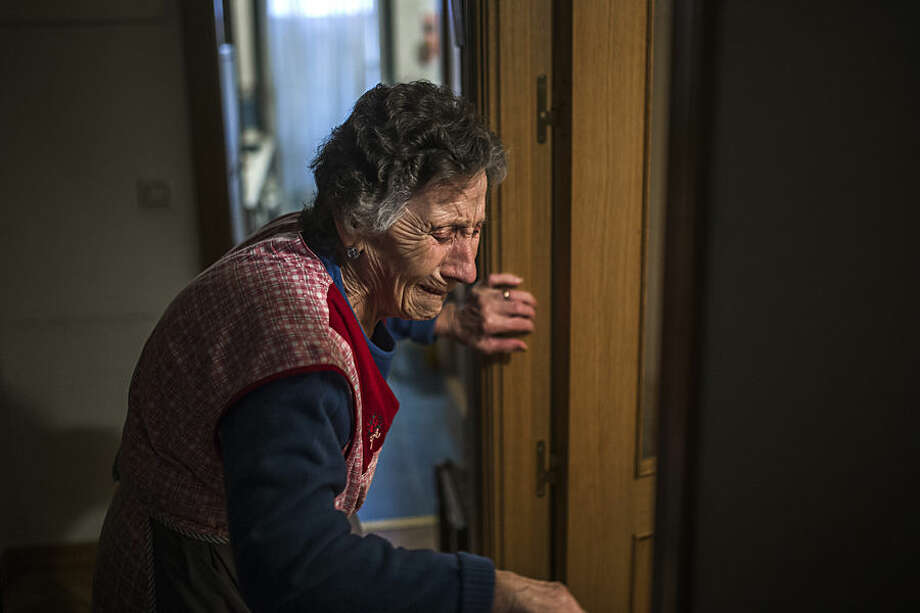 Carmen Martinez Ayudo, 85, cries during her eviction in Madrid, Spain, Friday, Nov. 21, 2014. Carmen Martinez Ayudo, who lives with a pension of euro 630 a month ($ 783) lost her foreclosed apartment to a moneylender after she could not afford to pay her debt and the high interest rates due to her financial situation after her son lost his job. Martinez Ayudo was evicted in spite of housing right activists clashing with the dozens of riot police. (AP Photo/Andres Kudacki)