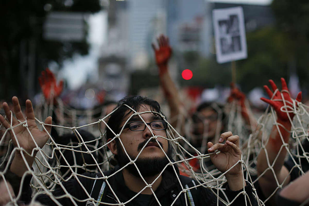Protesters walk under a giant net and with their hands painted red during a massive march in Mexico City,Thursday, Nov. 20, 2014. Mexico officially lists more than 22 thousand people as having gone missing since the start of the country's drug war in 2006, and the search for the missing students has turned up other, unrelated mass graves. (AP Photo/Dario Lopez-Mills)