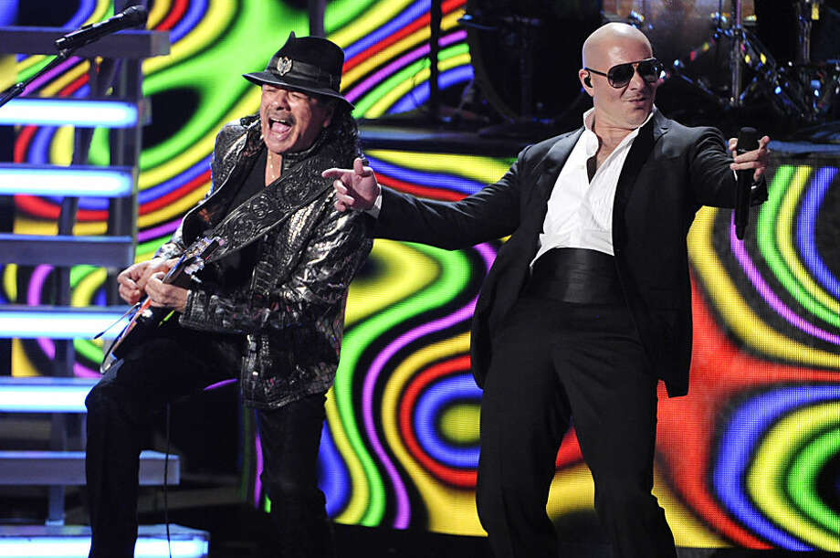 Carlos Santana, left, and Pitbull perform at the 15th annual Latin Grammy Awards at the MGM Grand Garden Arena on Thursday, Nov. 20, 2014, in Las Vegas. (Photo by Chris Pizzello/Invision/AP)