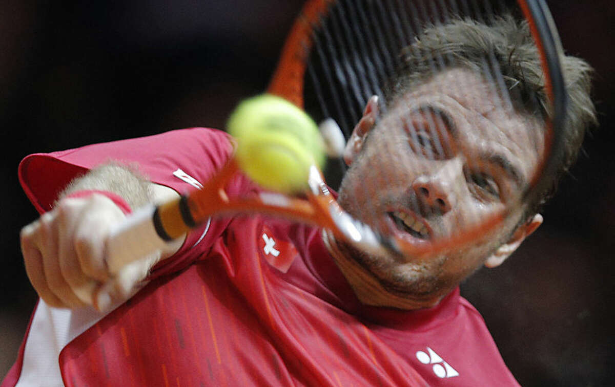Switzerland's Stanislas Wawrinka returns the ball to France's Jo-Wilfried Tsonga during the Davis Cup final in Lille, northern France, Friday, Nov.21, 2014. Switzerland is seeking a first victory in the team competition while France is looking for a 10th title. This is the 13th meeting between the two nations, with France leading 10-2. (AP Photo/Christophe Ena)