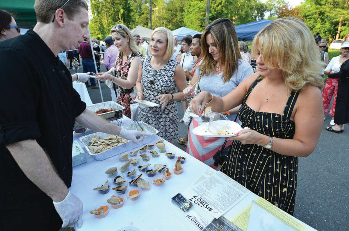 Chef Ian Doernberger places samples from Bistro 7 for guests to try at Taste of Wilton.