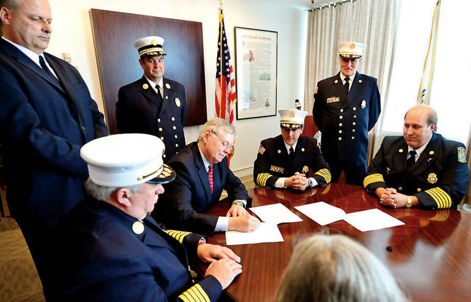 Mayor David Martin, Public Safety Director Ted Jankowski, Fire Chief Peter Brown, Turn Of River (TOR) Chief Frank Jacobellis, TOR Assistant Chief Matt Maounis, and TOR President Nicholas Jossem sign the agreement to consolidate the Stamford and Turn of River Volunteer Fire Departments.