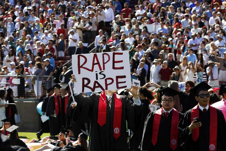 Paul Harrison (center) holds a sign protesting the prevalence of sexual assault on college campuses before the Stanford University Commencement in Stanford Stadium in Stanford, California, on Sunday, June 12, 2016. Photo: Connor Radnovich, The Chronicle