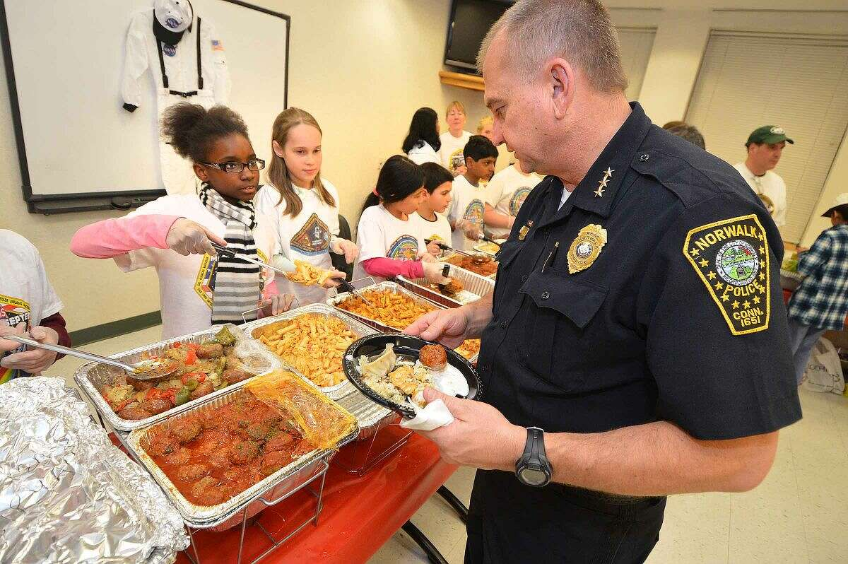 Hour Photo/Alex von Kleydorff Norwalk Police Chief Tom Kulhawik trys a little bit of everything served up by the Columbus Magnet School Young Astronauts at Police Headquarters
