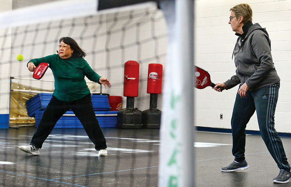 Hour photo / Erik Trautmann Dyanne Chang and Nancy Usic play Pickleball at the Norwalk Senior Center Friday. Senior Center members play for free and non-members who may be interested in the sport can play for a small fee. All seniors are welcome to join in the fun and lessons will be offered at various times for those who would like learn more about the game.