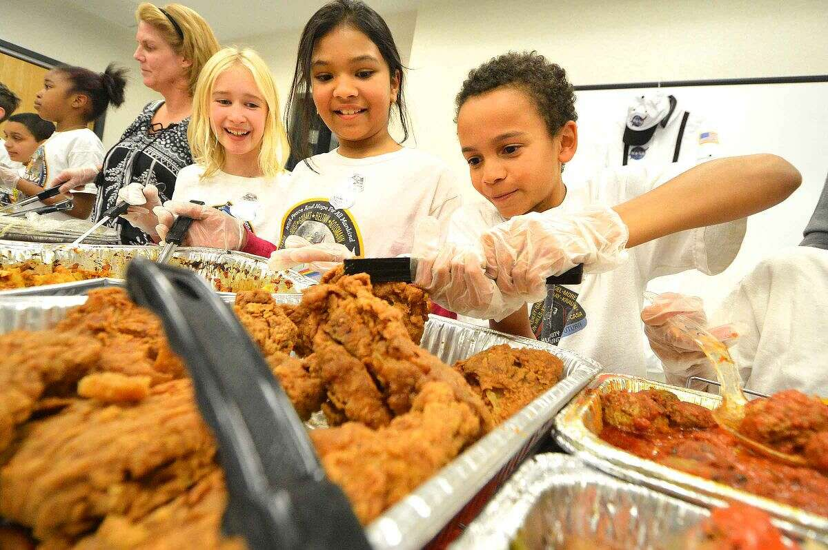 Hour Photo/Alex von Kleydorff Columbus Magnet School Young Astronaut Bailey Lewis handles the fried chicken for Norwalks First responders during the programs dinner at Police Headquarters