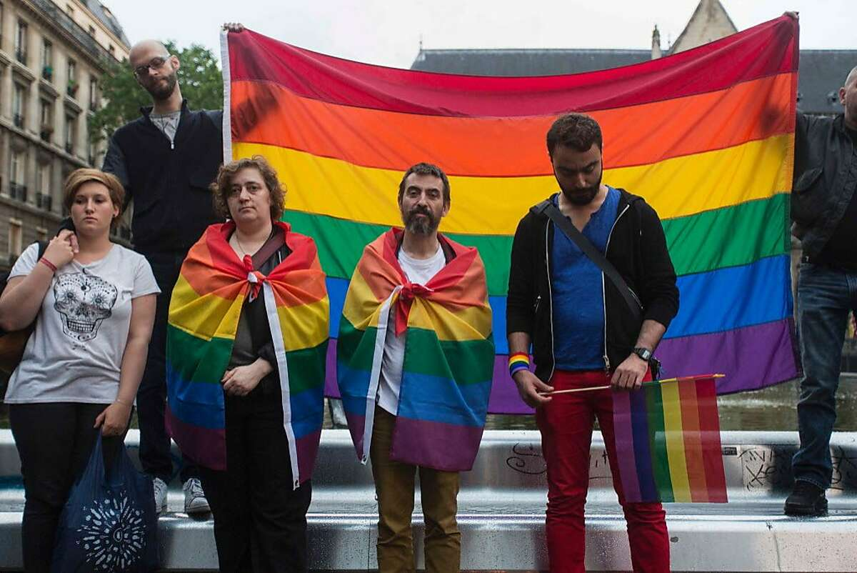 People and members of the gay community holding the peace rainbow flag gather for a vigil near the Beaubourg art center in downtown Paris on June 12, 2016, to mourn for victims of the mass shooting that occured overnight in Orlando, Florida, at the Pulse gay nightclub. Fifty people were killed, in addition to the shooter, and 53 wounded in the worst mass shooting in US history, the mayor of Orlando Buddy Dyer said earlier on June 12. A fighter from the Islamic State group carried out the mass shooting, the IS-linked news agency Amaq said, quoting an unidentified source.
