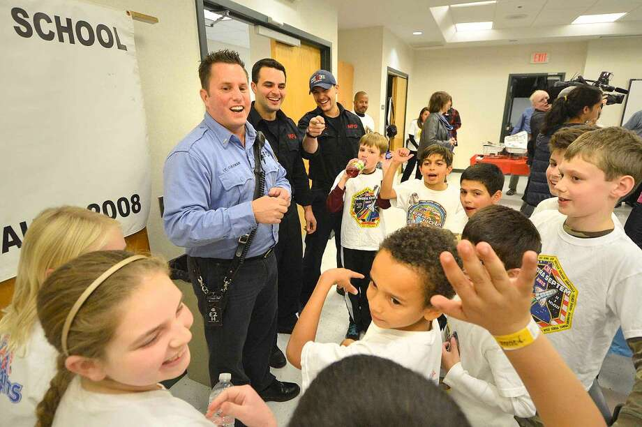 Hour Photo/Alex von Kleydorff Lt. Lenny Coleman and Firefighters Nick Lipeika and Anthony Papacoda from Station 2, talk about the program with some of the Columbus Magnet School Young Astrnauts