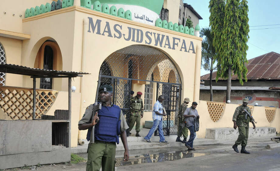 In this photo taken Wednesday, Nov. 19, 2014, armed police walk out of the Masjid Swafaa mosque after raiding it, in Mombasa, Kenya. Methods used by Kenyan authorities to tackle extremism on the country's coast will increase support for radicals, a human rights official warned Friday, Nov. 21, 2014, after authorities raided and closed four mosques over the last week, in which the police said they recovered grenades and a gun but some muslims allege were planted in order to justify the mosques' closures. (AP Photo)