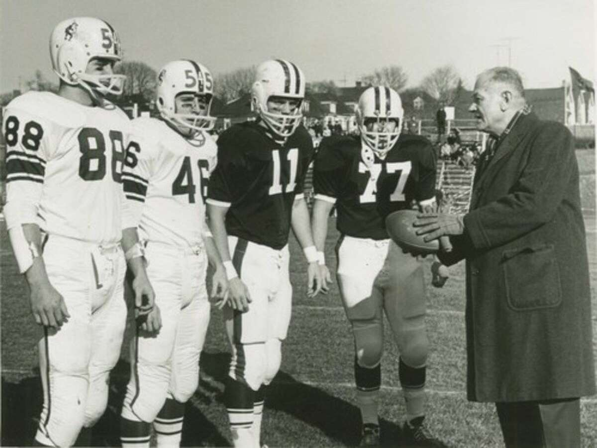 In this Nov. 21, 1964, photo provided by Lafayette College, Lehigh co-captains Chuck Ortlan (88) and Joe Weiss (46) along with Lafayette co-captains George Hossenlopp (11) and Douglas Dill (77) present the ball to College Football Hall of Fame president Harvey Harmon after the kickoff in the 100th game between the two small Division I schools in Easton, Pa. The 150th game between the schools is Saturday, Nov. 22, 2014, at Yankee Stadium in New York. (AP Photo/Lafayette College Archives)