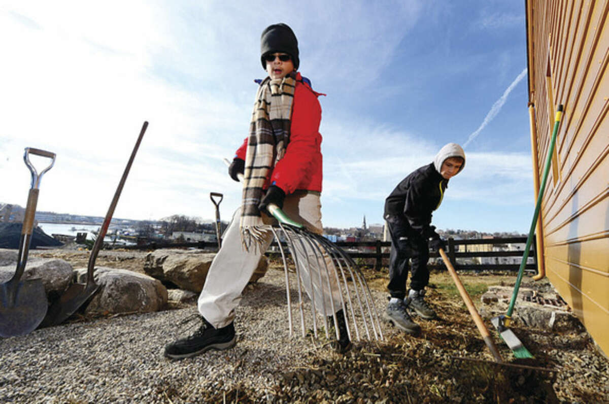Hour photo / Erik Trautmann Boy Scouts from Troop 2, Bhavesh Rethore and Connor Inglis, help Scout Nicholas Miklave with his Eagle Scout project at the Mill Hill historic complex Saturday.