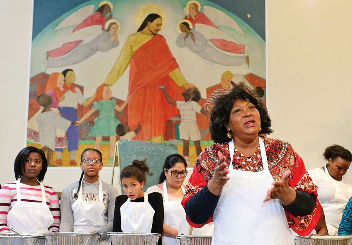 Hour photo / Erik Trautmann The Rev. Nellie Mann gives the blessing as she opens the annual Heart to Heart Pre-Thanksgiving Day luncheon for the less fortunate at the Calvary Baptist Church Saturday