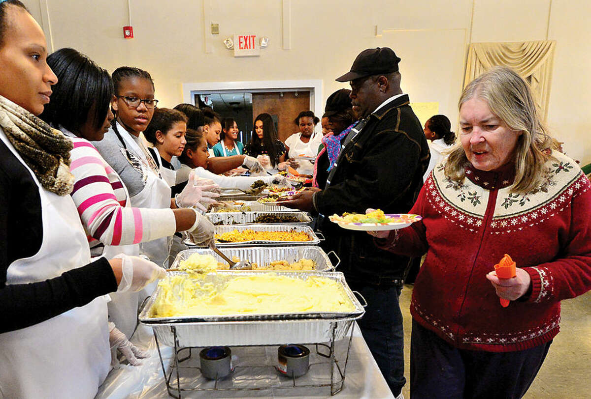 Hour photo / Erik Trautmann Cheryl Kuziak, right, looks over the plentiful food during The Rev. Nellie Mann's annual Heart to Heart Pre-Thanksgiving Day luncheon for the less fortunate at the Calvary Baptist Church Saturday.