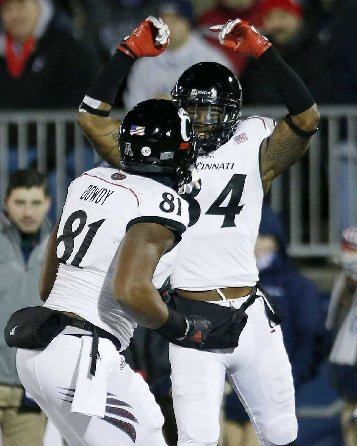 Cincinnati wide receiver Nate Cole (84) celebrates his touchdown with tight end DJ Dowdy (81) in the first quarter of an NCAA college football game against Connecticut in East Hartford, Conn., Saturday, Nov. 22, 2014. (AP Photo/Michael Dwyer)