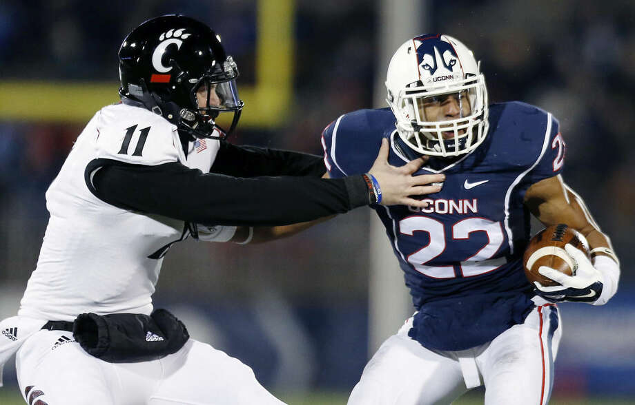 Connecticut safety Andrew Adams (22) breaks a tackle on Cincinnati quarterback Gunner Kiel (11) after intercepting Kiel's pass in the first quarter of an NCAA college football game in East Hartford, Conn., Saturday, Nov. 22, 2014. (AP Photo/Michael Dwyer)