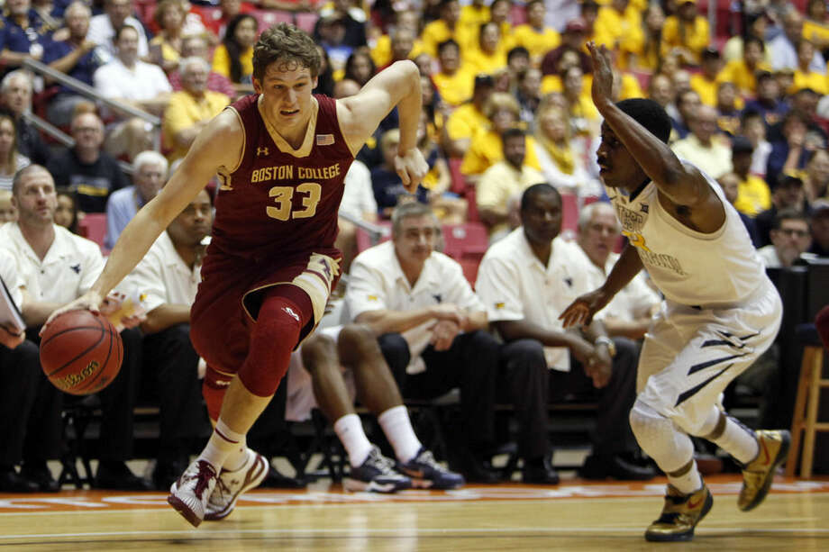 Boston College guard Patrick Heckmann, left, dribbles past West Virginia guard Juwan Staten at a NCAA college basketball game in San Juan, Puerto Rico, Friday, Nov. 21, 2014. (AP Photo/Ricardo Arduengo)