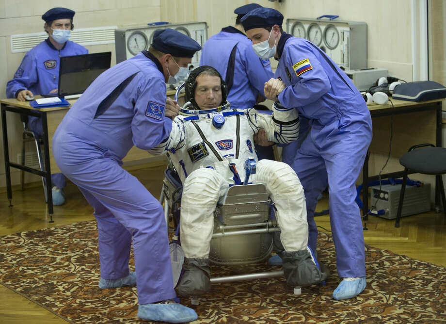 Russian Space Agency experts help U.S. astronaut Terry Virts, crew member of the mission to the International Space Station, ISS, to stand up after inspecting his space suit prior to the launch of Soyuz-FG rocket at the Russian leased Baikonur cosmodrome, Kazakhstan, Sunday, Nov. 23, 2014. (AP Photo/Dmitry Lovetsky, Pool)