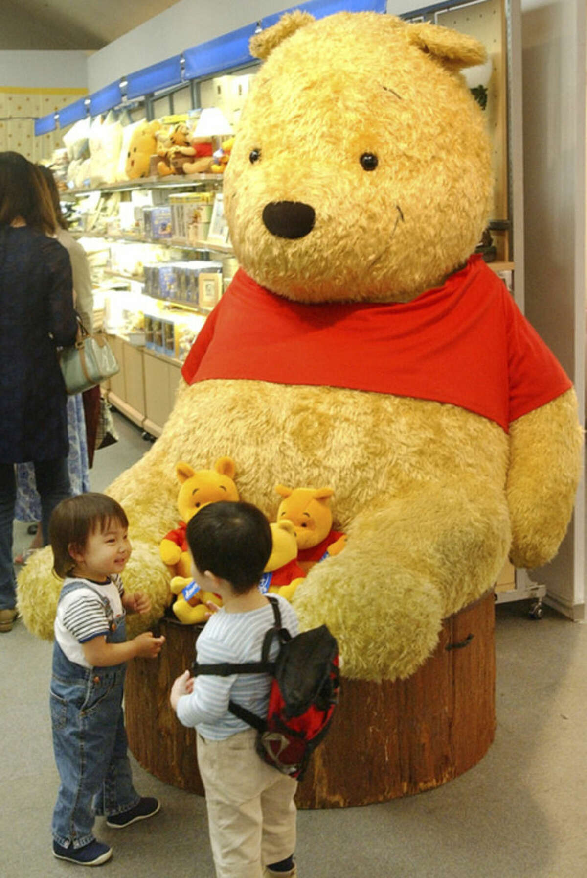 FILE - Two boys chat in front of a giant stuffed doll of Winnie-The-Pooh at the
