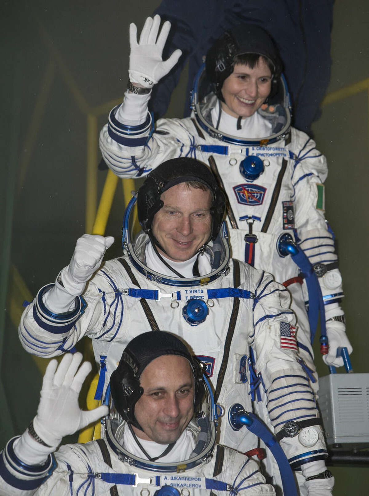 U.S. astronaut Terry Virts, centre, Russian cosmonaut Anton Shkaplerov, bottom, and Italian astronaut Samantha Cristoforetti, crew members of the mission to the International Space Station, ISS, gesture prior the launch of Soyuz-FG rocket at the Russian leased Baikonur cosmodrome, Kazakhstan, Monday, Nov. 24, 2014. (AP Photo/Shamil Zhumatov, Pool)