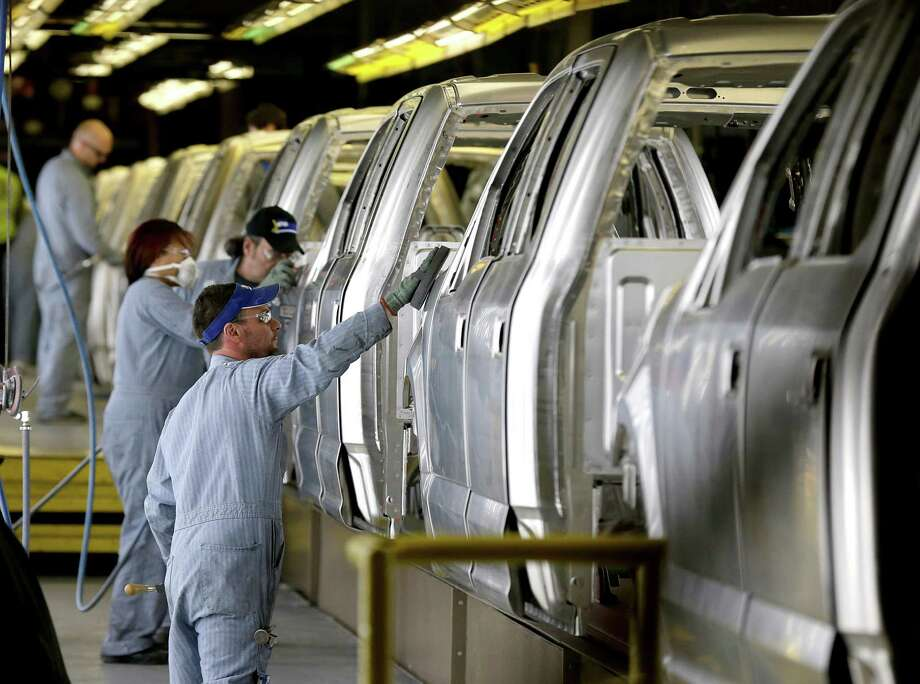 Workers inspect the new aluminum-alloy body Ford F-150 trucks before they get painted at the company's Kansas City Assembly Plant in Claycomo, Mo. General Motors Co. has launched a series of ads showing field tests in which the steel Chevy Silverado pickup holds up better under heavy workloads than Ford's aluminum-bodied model. Photo: Associated Press File Photo / AP