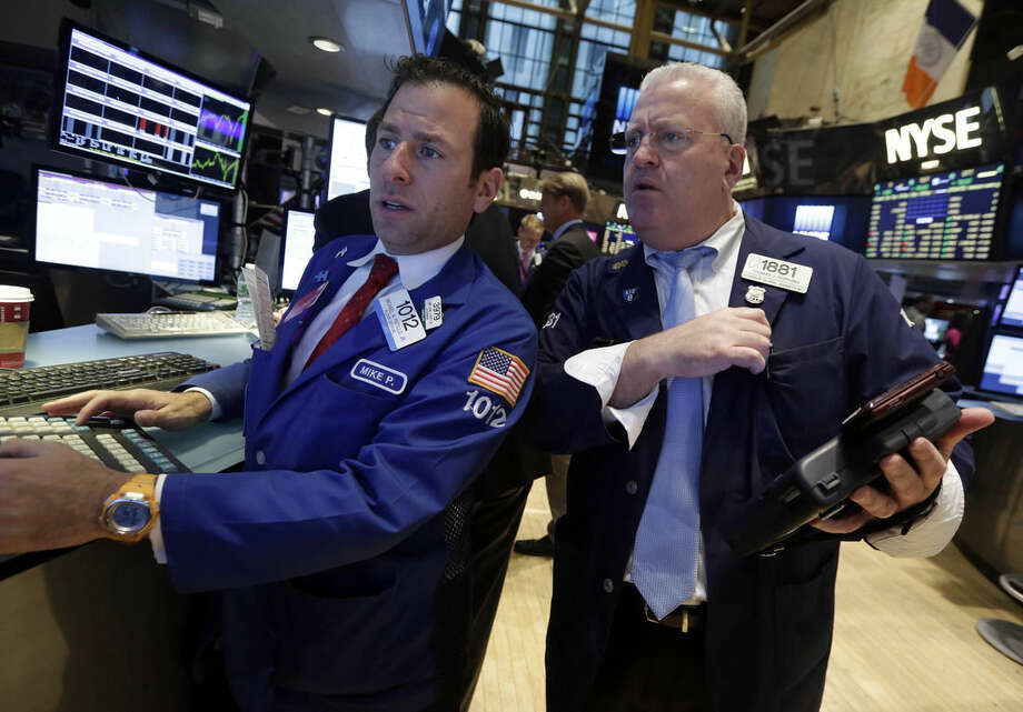 Specialist Michael Pistillo, left, and trader Thomas Ferrigno work on the floor of the New York Stock Exchange, Monday, Nov. 24, 2014. U.S. stocks rose in early trading in line with gains from Asian markets and thanks to improvement in German business confidence. (AP Photo/Richard Drew)