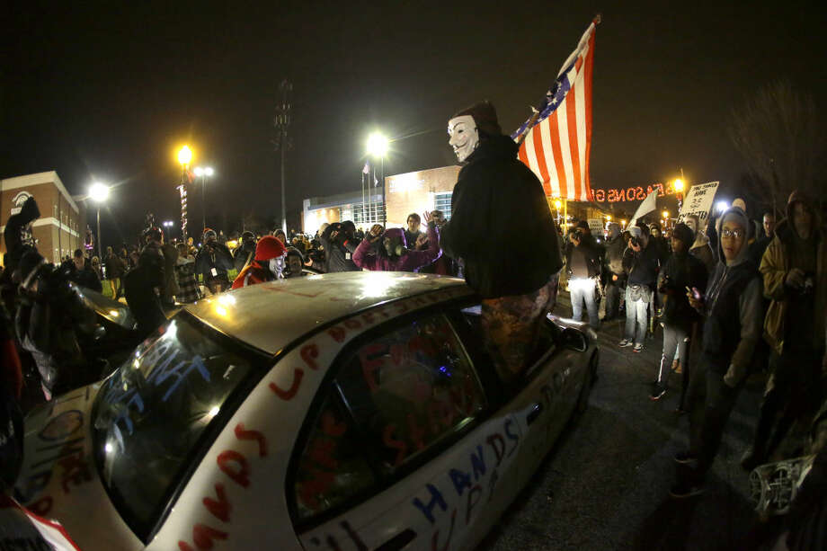 Protesters gather in front of the Ferguson Police Department before the announcement of the grand jury decision about whether to indict a Ferguson police officer in the shooting death of Michael Brown, Monday, Nov. 24, 2014, in Ferguson, Mo. A Missouri grand jury heard evidence for months as it weighed whether to indict Ferguson police Officer Darren Wilson in the Aug. 9 fatal shooting of Brown, which was followed by sometimes violent protests. (AP Photo/Charlie Riedel)