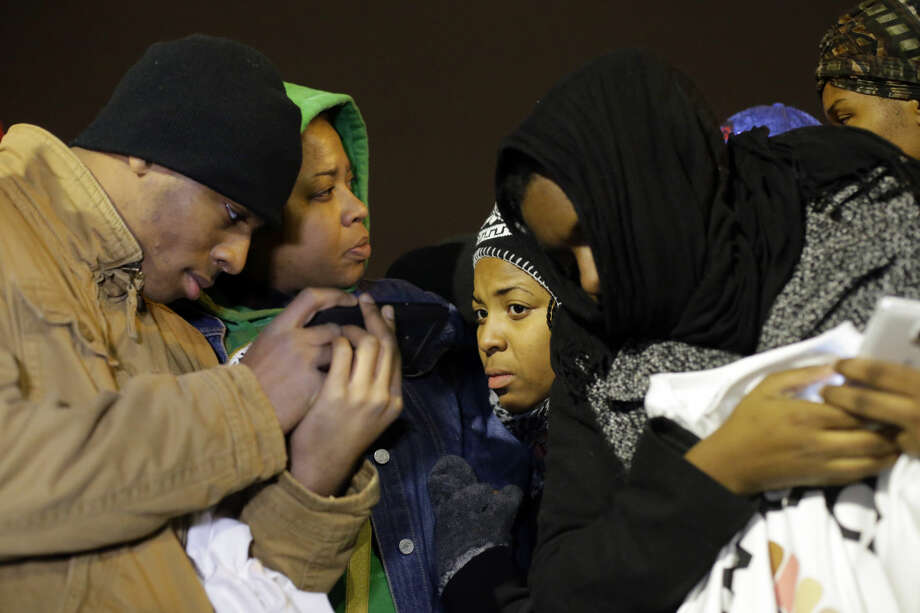 Protesters listen to the announcement of the grand jury decision Monday, Nov. 24, 2014, in Ferguson, Mo. A grand jury has decided not to indict Ferguson police officer Darren Wilson in the death of Michael Brown, the unarmed, black 18-year-old whose fatal shooting sparked sometimes violent protests. (AP Photo/Charlie Riedel)
