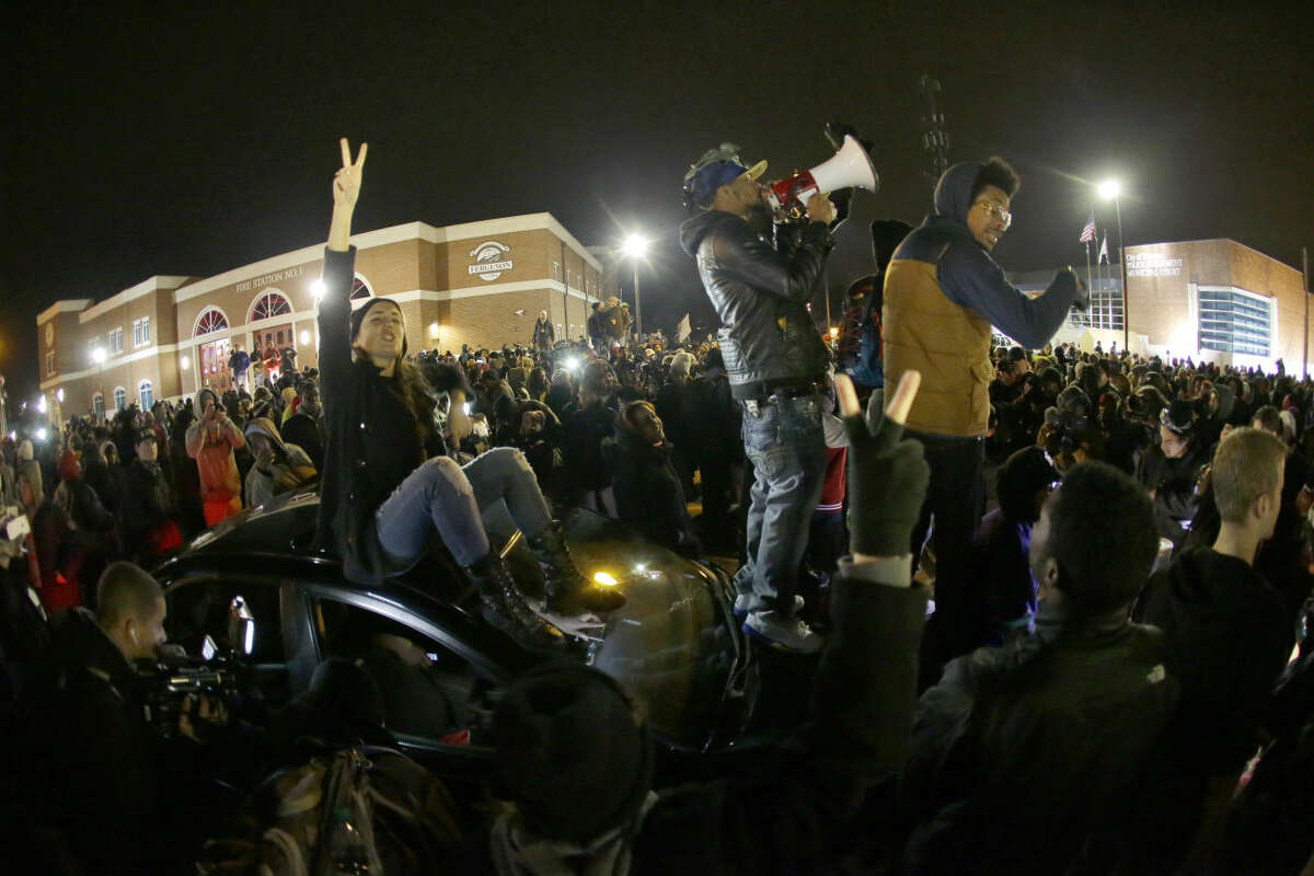 Protesters gather in front of the Ferguson Police Department before the announcement of the grand jury decision about whether to indict a Ferguson police officer in the shooting death of Michael Brown, Monday, Nov. 24, 2014, in Ferguson, Mo. A Missouri grand jury heard evidence for months as it weighed whether to indict Ferguson police Officer Darren Wilson in the Aug. 9 fatal shooting of Brown. (AP Photo/Charlie Riedel)