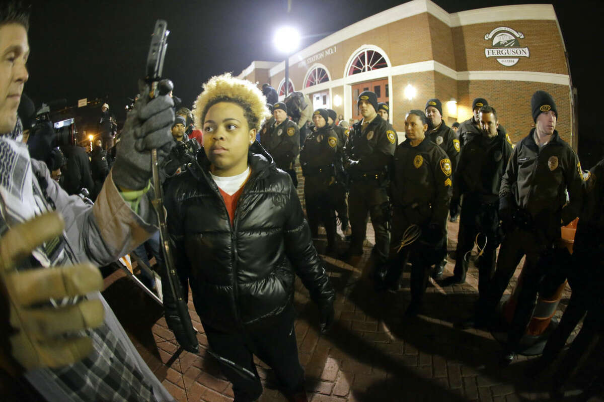 Police line up in front of the Ferguson Police Department before the announcement of the grand jury decision about whether to indict a Ferguson police officer in the shooting death of Michael Brown, Monday, Nov. 24, 2014, in Ferguson, Mo. A Missouri grand jury heard evidence for months as it weighed whether to indict Ferguson police Officer Darren Wilson in the Aug. 9 fatal shooting of Brown. (AP Photo/Charlie Riedel)