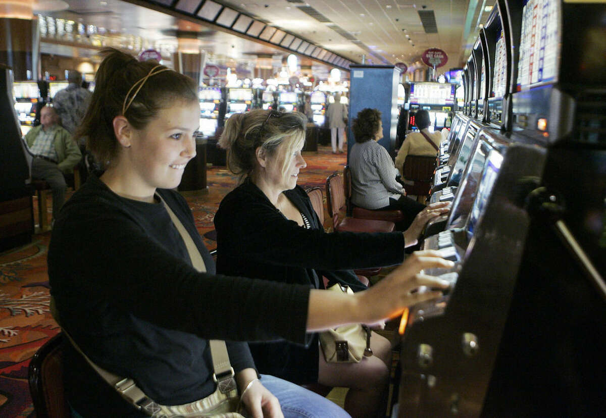 FILE - In this Aug. 30, 2009 file photo, Caitlin and Lynne Byers play the slot machines at Foxwoods Resort and Casino in Mashantucket, Conn. Foxwoods, North America's largest casino resort, is reducing the number of slot machines and table games to free up space for nightclubs and other new attractions as it adapts to fierce competition from neighboring states, the new CEO said in an interview Monday, Nov. 24, 2014 with The Associated Press. (AP Photo/Bob Child, file)