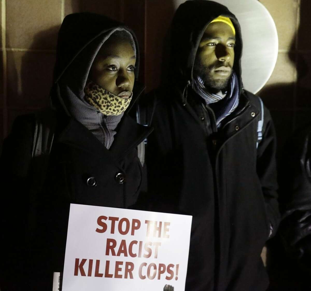 Monet Felton, left, and Jo Schaffer gather outside the Chicago Police headquarters for a protest before the announcement of the grand jury decision not to indict police officer Darren Wilson in the fatal shooting of Michael Brown Monday, Nov. 24, 2014, in Chicago. (AP Photo/Charles Rex Arbogast)
