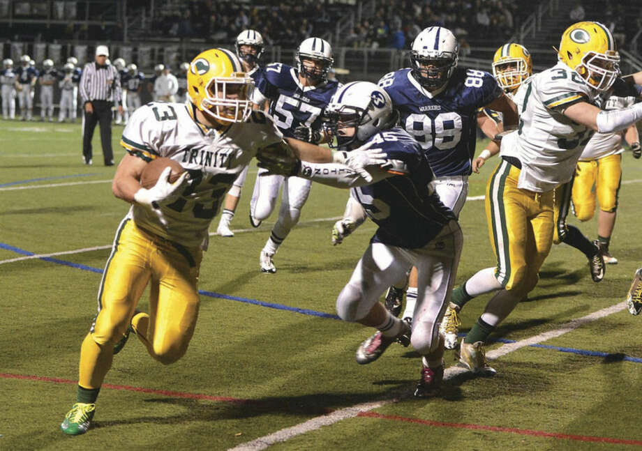 Hour Photo/Alex von KleydorffTrinity Catholic's Justin Przypek, left, rushes for a touchdown on Tuesday night at Fujitani Field.