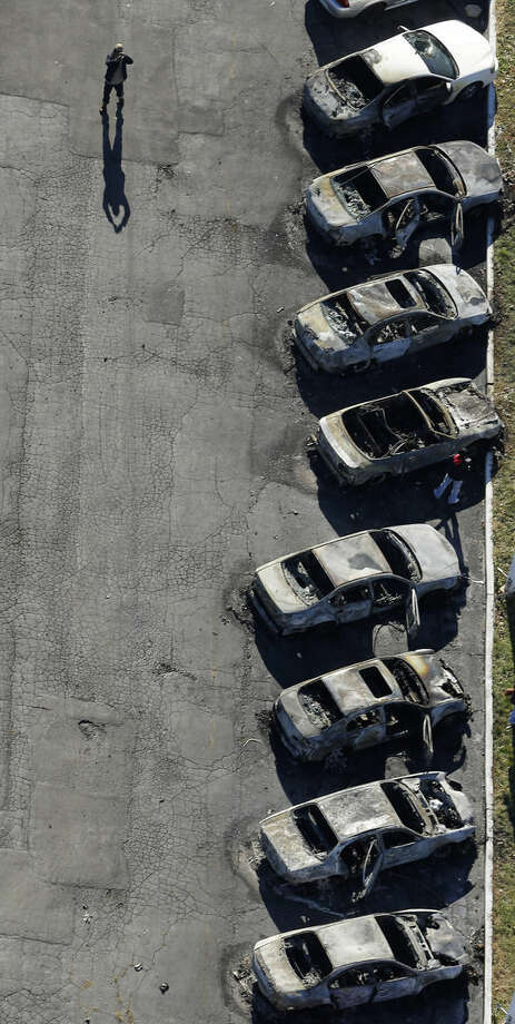 In this aerial photo, person takes photos of a row of charred cars at a used car dealership Tuesday, Nov. 25, 2014, in Dellwood, Mo., after they were burned in overnight protests following a grand jury's decision not to indict a white police officer in the killing of unarmed black 18-year-old Michael Brown. Monday night's protests were far more destructive than any of those that followed Brown's Aug. 9 death, with more than a dozen businesses badly damaged or destroyed. (AP Photo/Charlie Riedel)