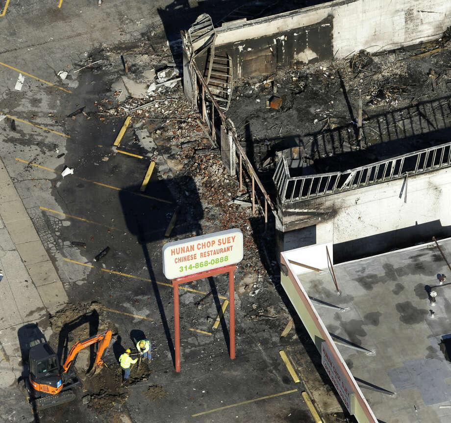 In this aerial photo, workers dig in the parking lot of a building Tuesday, Nov. 25, 2014, in Ferguson, Mo., after it was burned in overnight protests following a grand jury's decision not to indict a white police officer in the killing of unarmed black 18-year-old Michael Brown. Monday night's protests were far more destructive than any of those that followed Brown's Aug. 9 death, with more than a dozen businesses badly damaged or destroyed. (AP Photo/Charlie Riedel)