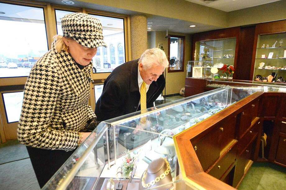 Hour Photo/Alex von Kleydorff Mayor Harry Rilling and Elizabeth Stocker, Director of Economic Development look at a display case of fine jewlery during a visit to David Harvey Jewlers as part of a promotion for Small Businees Saturday